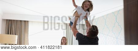 Man Tosses Laughing Child Over His Head In Bedroom. Family Relationships And Positive Atmosphere At