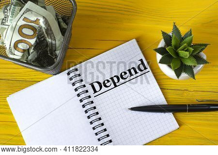 Depend - Written In A Notebook On A Yellow Wooden Background With A Cactus And A Stationery Basket W