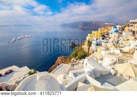 Panoramic view of Santorini. The famous town of Oia in the morning. A line of sailing yachts at sea. Good vacation. Oia, Santorini, Greece