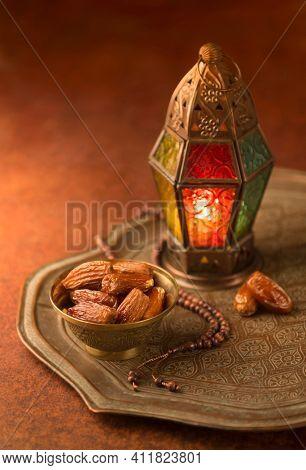 Fanoos. An illuminated Ramadan decorative lamp and dates in an old, antique tray.Ramadan background - stock photo