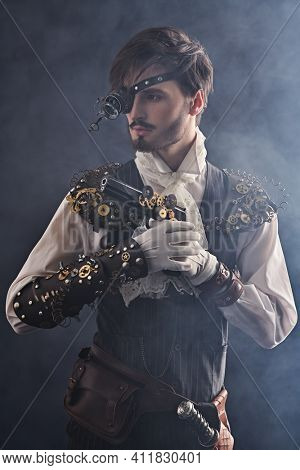 Steampunk man. Portrait of a handsome noble man with steampunk gadgets and a gun on a dark background with haze.