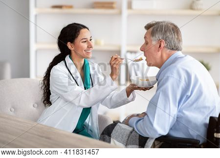 Medical Assistance For Elderly People With Disabilities. Young Nurse Feeding Senior Handicapped Man