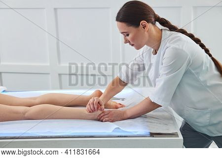 Female Masseur Is Performing A Heel Squeeze