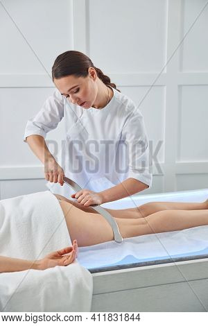 Massage Therapist Doing Careful Scraping Movements With Tool On Leg