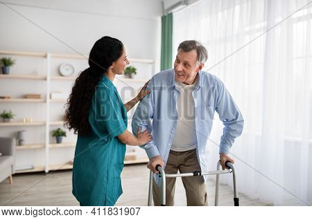 Young Nurse Helping Older Man To Walk With Frame At Retirement Home. Mature Male Petient With Caregi
