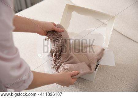 Woman Taking Soft Cashmere Sweater Out Of Box Indoors, Closeup