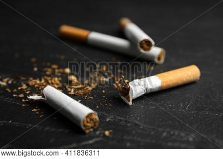 Broken And Whole Cigarettes On Black Table, Closeup. Quitting Smoking Concept
