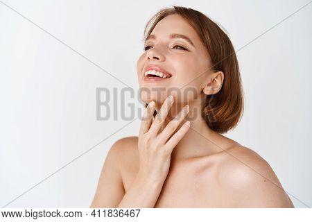 Skin Care Beauty. Beautiful Natural Woman Touching Neck And Smiling, Looking Aside. Girl Laughing An