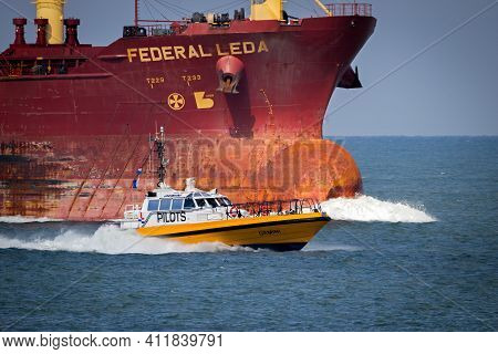Pilot Boat With Maritime Pilots Transfering Between The Inbound And Outbound Ship In The Port Of Rot