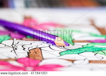 A Portrait Of A Purple Pencil Lying On A Coloring Book For Adults. The Page Is Already A Bit Colored