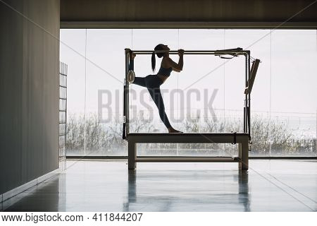 Full Shot Of A Big Fitness Gym With Wide Windows And Street Views, With A Fit Female Pilates Instruc