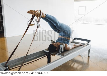 Rear View Of A Fit Woman Lying Down On A Bed Of A Pilates Reformer Machine Bed, With Legs Up, Workin