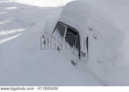Snow Covered Passenger Car On A Winter Road Close Up