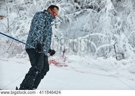 A Skier In Gray Jacket Is Riding Downhill The Slope On A Frosty Day