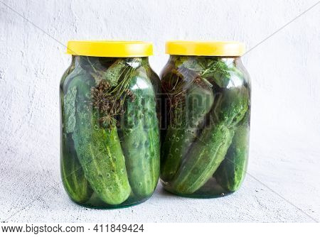 Two Glass Jars With Pickled Cucumbers, Covered With Lids. The Concept Of Preserving Organic Products