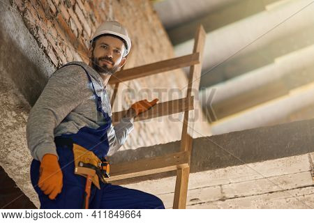 Construction You Can Count On. Handsome Workman In Blue Overalls And Hard Hat Looking At Camera, Cli