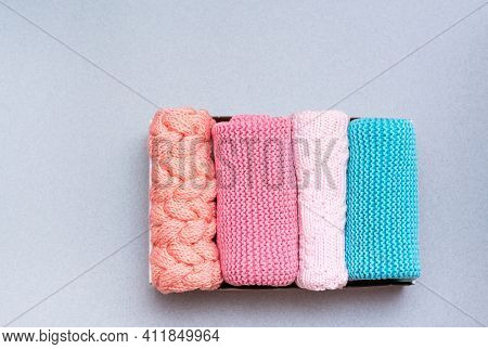 Organization And Order. Knitted Clothes Lie Neatly Folded In A Box On A Gray Background. Top View
