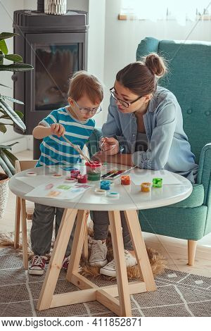 Mother Or Art Therapist And Child Paint Watercolor Together At H