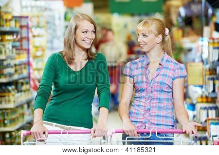 two smiling women choosing food produces in shopping mall with supermarket trolley