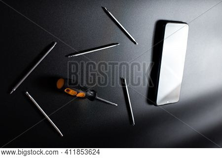 Screwdrivers And Other Tools For Reparing Smsartphones On Black Background.