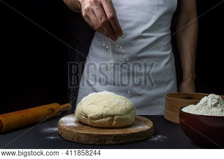Dough On A Dark Background. A Man\'s Hand Sprinkles Flour On The Dough. Chef Working With Dough On B