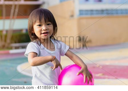 Happy Asian Baby Child Girl Playing And Kicking A Ball Toys At The Field Playground. She Smiling A