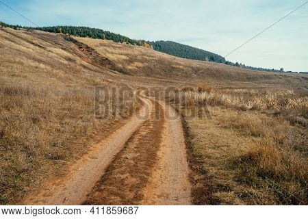 Dirt Road In The Steppe. Landscape With A Wide Dirt Road Going Through The Steppe Up To The Hills.