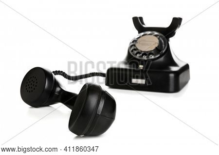 Vintage black telephone with receiver off-hook isolated on white background, selective focus