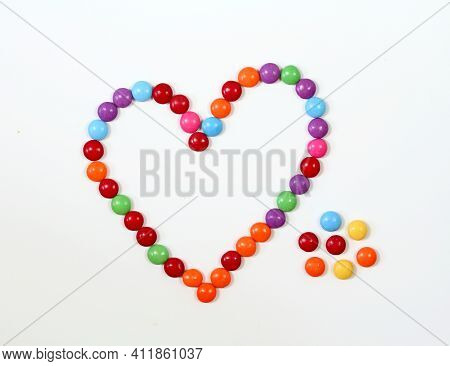 Sweet Heart Made From Colored Smarties. Chocolate Candies In A Shape Of Heart On White Background, F
