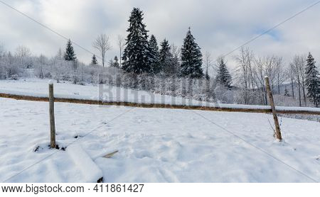 Landscape with wooden fence on winter meadow in mountains