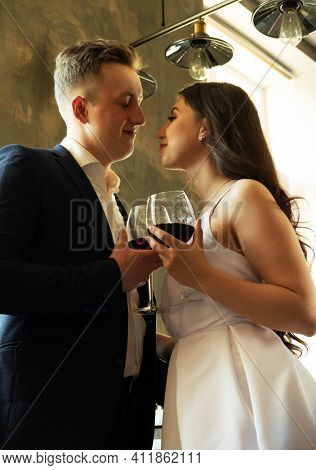 Young newlywed couple drinking wine and smiling at their happiness, romance and tenderness.