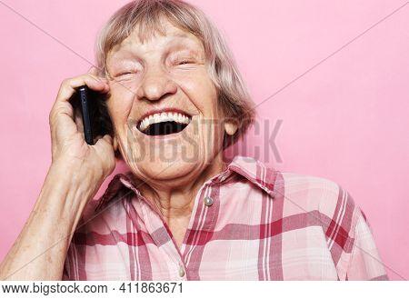 Modern Communication. Happy senior woman using mobile phone over pink background. Beautiful stylish elderly lady talking on cellphone.