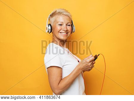 Old people, emotion and technology concept: portrait of happy senior woman listening to music with headphones