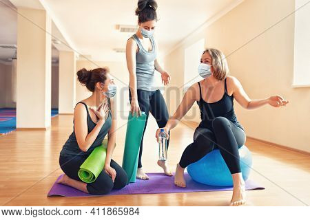 New Normal. A Group Of Young Women In Protective Masks Communicate In A Yoga Studio. The Concept Of