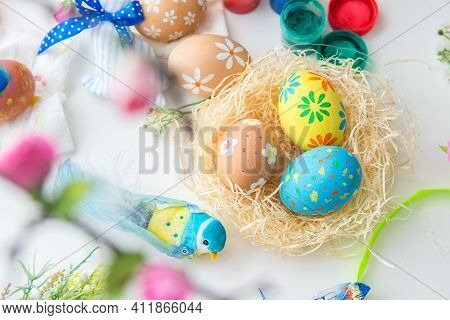 Multicolored Easter Painted Handmade Eggs In Bird's Nest, Easter Decorations, Paints And Brushes On