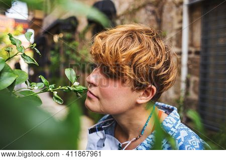 Portrait Of A Girl Sniffing Flowers, A Walk In A Spring Park, A Red-haired Woman Feels The Aroma Of