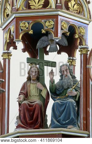 OSTARIJE, CROATIA - JULY 14, 2013: Holy Trinity, statue on the baptistery in Our Lady of Miracles Parish in Ostarije in Croatia