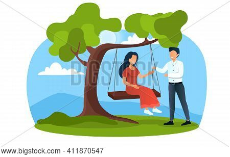 Young Happy Couple On A Swing In Park Outdoors. Smiling Man Is Swinging His Girlfriend Near Big Tree
