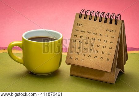 August 2021 - spiral desktop calendar against abstract paper landscape with a cup of coffee, time and business concept
