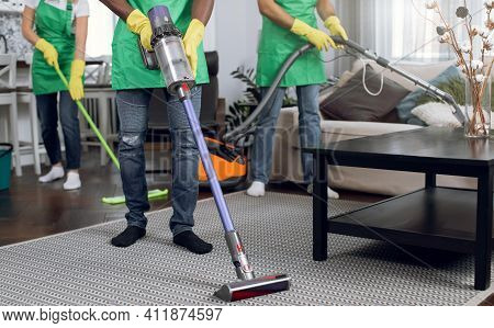 Close Up Of Cleaners In Green Apron And Yellow Gloves Using Vacuum Cleaner, Mop And Rag While For Hy