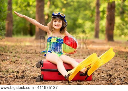 Little Child Girl Wear Swimsuit Sitting On Suitcase In Summer Forest With Hands Up, Show Plane. Drea
