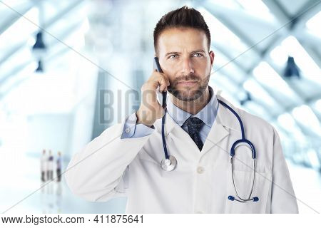 Shot Of Male Doctor Talking With Somebody On His Mobile Phone While Standing On The Clinic's Foyer.