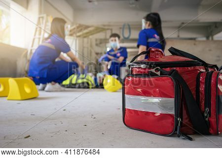 Selective Focus Is First Aid Bag. Team Paramedic Firs Aid Employee Accident In Construction Site Wor