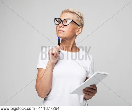 Lifestyle, education and old people concept: senior female teacher writing notes in organizer wearing glasses