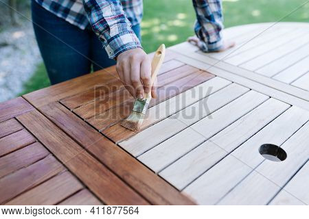 Renovation Of A Garden Table With A Paintbrush And Oil By A Young Girl
