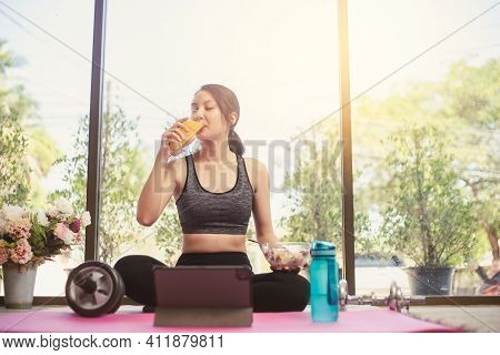 Healthy Asian Woman In Sportswear Sitting On The Yoga Mat Drinking Orange Juice And Eating Salad Fru