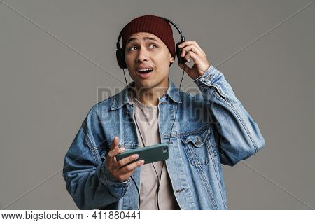 Perplexed handsome guy listening music with headphones and cellphone isolated over grey background