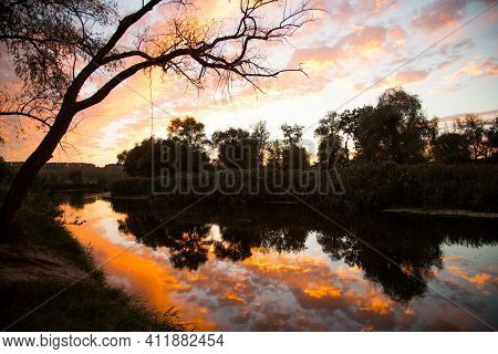 Incredibly Beautiful Sunset On The River. Reflection Of Orange-red Clouds In The River. Play Of Colo