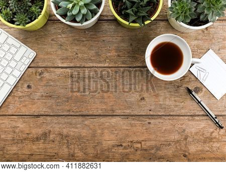 Wooden hipster desk with computer keyboard, tea cup, potted succulent plant and stationery. Top view with copy space , flat lay.