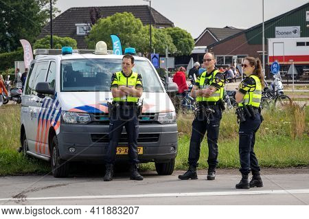 Volkel, Netherlands - Jun 15, 2019: Dutch Police Men And Woman On Watch Near Their Police Car During